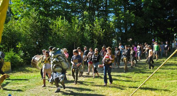 a parade of people through a grassy area by the forest some in costume and some playing instruments