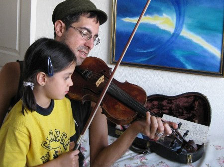 Michael Imserio teaches fiddle to a young girl