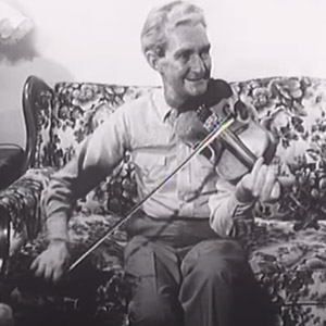 Old time musician Earl Collins sitting on the couch and playing fiddle