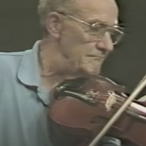 Headshot of old time music fiddler Wilson Douglas playing fiddle
